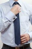 Homem de negócios que ajusta o laço imagens de stock royalty free