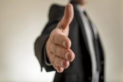 Homem de negócios que alcanga para fora para agitar as mãos fotos de stock royalty free
