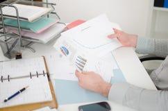 Homem de negócios que analisa gráficos Fotografia de Stock Royalty Free