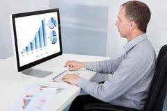 Homem de negócios que analisa o gráfico no computador Fotos de Stock Royalty Free