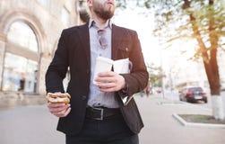 Homem de negócios que anda abaixo da rua com um petisco e um café em suas mãos imagem de stock
