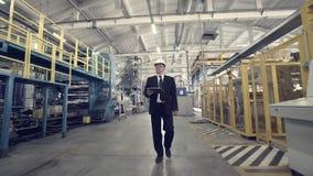 Homem de negócios que anda através da fábrica filme