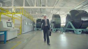 Homem de negócios que anda através da fábrica e que fala no telefone vídeos de arquivo