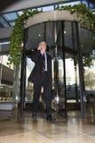 Homem de negócios que anda através da porta giratória. imagens de stock royalty free