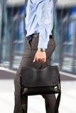 Homem de negócios que anda e que guarda uma pasta de couro em seu han Fotografia de Stock