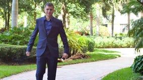 Homem de negócios que anda em um jardim vídeos de arquivo