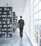 Homem de negócios que anda na biblioteca Imagem de Stock Royalty Free