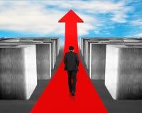 Homem de negócios que anda na seta vermelha através do labirinto 3d Imagens de Stock