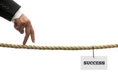 Homem de negócios que anda seus dedos ao longo de um comprimento da corda ou de um tigh Fotografia de Stock