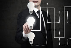 Homem de negócios que aponta à lâmpada de incandescência Imagem de Stock Royalty Free