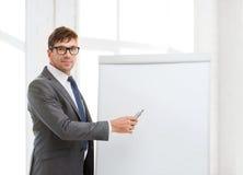 Homem de negócios que aponta à placa da aleta no escritório Fotografia de Stock