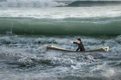 Homem de negócios que aponta o assento no barco do dinheiro no oceano com ondas imagem de stock royalty free