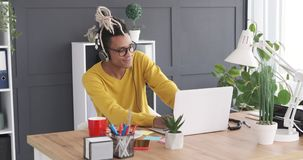 Homem de negócios que aprecia a música usando fones de ouvido e portátil do escritório video estoque