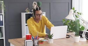 Homem de negócios que aprecia a música usando fones de ouvido e portátil no escritório video estoque