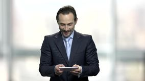 Homem de negócios que aprecia o jogo online video estoque