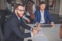Homem de negócios que apresenta aos colegas em uma reunião Fotografia de Stock Royalty Free