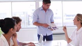 Homem de negócios que apresenta a carta à equipe do negócio video estoque