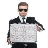 Homem de negócios que apresenta a mala de viagem do metal completamente do dinheiro Foto de Stock Royalty Free