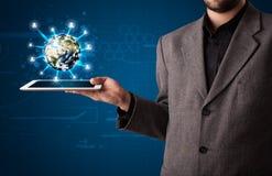 Homem de negócios que apresenta o globo da terra 3d na tabuleta Fotografia de Stock Royalty Free