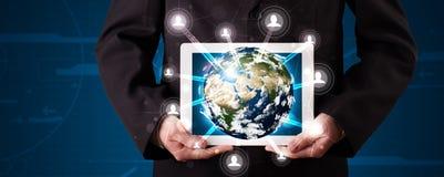 Homem de negócios que apresenta o globo da terra 3d na tabuleta Imagens de Stock Royalty Free