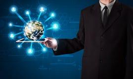 Homem de negócios que apresenta o globo da terra 3d na tabuleta Fotografia de Stock