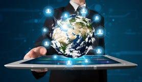 Homem de negócios que apresenta o globo da terra 3d na tabuleta Imagens de Stock