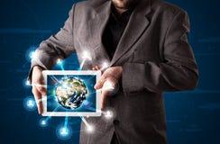 Homem de negócios que apresenta o globo da terra 3d na tabuleta Foto de Stock