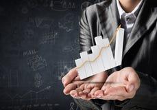Homem de negócios que apresenta o gráfico crescente Fotografia de Stock Royalty Free