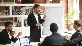 Homem de negócios que apresenta o plano novo do projeto aos sócios diversos com flipchart video estoque