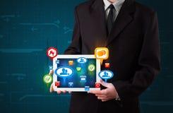 Homem de negócios que apresenta a tabuleta moderna com sinais sociais coloridos Fotos de Stock Royalty Free