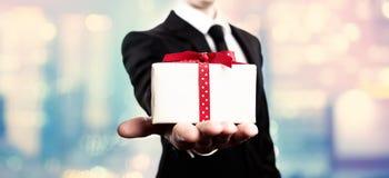 Homem de negócios que apresenta uma caixa de presente Fotografia de Stock Royalty Free