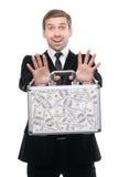 Homem de negócios que apresenta uma mala de viagem completamente de cem dólares americanos Imagens de Stock Royalty Free
