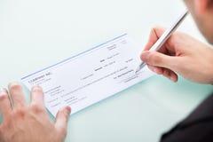 Homem de negócios que assina no cheque Fotografia de Stock Royalty Free