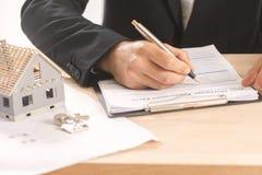 Homem de negócios que assina um contrato da hipoteca Imagem de Stock