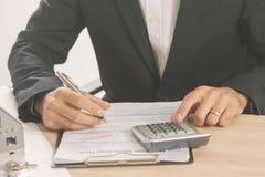 Homem de negócios que assina um contrato da hipoteca Foto de Stock