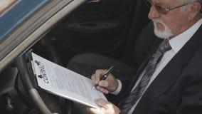 Homem de negócios que assina um contrato que senta-se no carro O chefe faz um acordo vídeos de arquivo