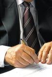 Homem de negócios que assina um formulário Fotografia de Stock