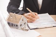 Homem de negócios que assina uma hipoteca Fotografia de Stock Royalty Free