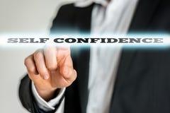 Homem de negócios que ativa um botão da autoconfiança em seixos virtuais foto de stock royalty free