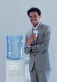 Homem de negócios que bebe de um refrigerador de água no escritório fotografia de stock royalty free