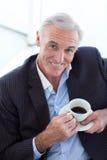 Homem de negócios que bebe e que senta-se em uma sala de espera Fotografia de Stock