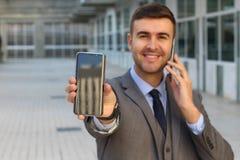Homem de negócios que chama e que mostra uma segunda tela do telefone celular imagens de stock