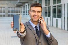 Homem de negócios que chama e que mostra uma segunda tela do telefone celular foto de stock royalty free
