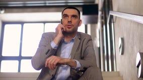 Homem de negócios que chama o smartphone em escadas do escritório filme