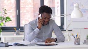 Homem de negócios que chama o smartphone no escritório vídeos de arquivo