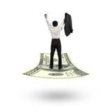 Homem de negócios que cheering e que está no tapete de voo do dinheiro imagem de stock royalty free