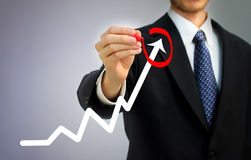Homem de negócios que circunda uma seta de aumentação imagem de stock royalty free