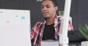 Homem de negócios que cola a nota adesiva no portátil e que bebe o café no escritório video estoque