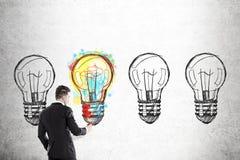 Homem de negócios que colore um de quatro bulbos foto de stock royalty free