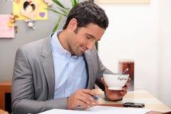 Homem de negócios que come o café antes do trabalho Fotos de Stock Royalty Free